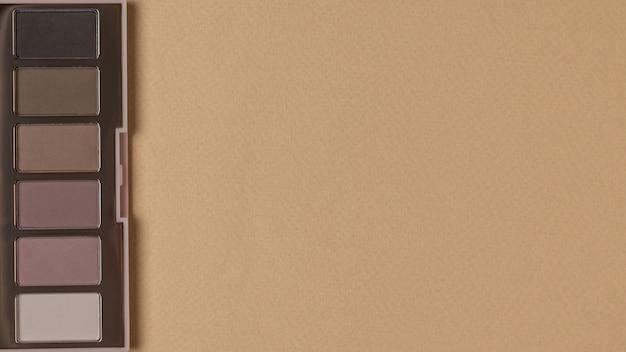Vista superior de um conjunto de sombras em tons pastel sobre fundo bege. cosméticos femininos elegantes. espaço para texto.