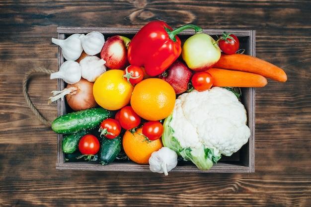 Vista superior de um conjunto de vegetais e frutas em uma caixa de madeira sobre uma mesa de madeira