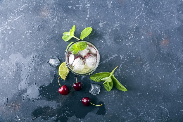 Vista superior de um copo de limonada de verão ou chá gelado em plano de fundo texturizado cinza