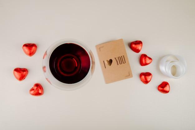 Vista superior de um copo de vinho com bombons de chocolate em forma de coração embrulhados em papel alumínio vermelho e um pequeno cartão postal na mesa branca