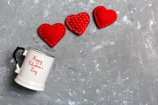 Vista superior de um copo e corações vermelhos caindo dele