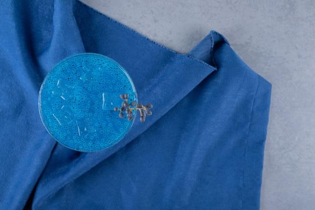 Vista superior de um coquetel azul fresco em um guardanapo de algodão azul