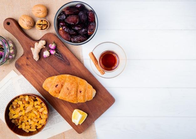 Vista superior de um croissant em uma tábua de madeira com tâmaras secas doces e passas em taças, armudu copo de chá em madeira branca com espaço de cópia