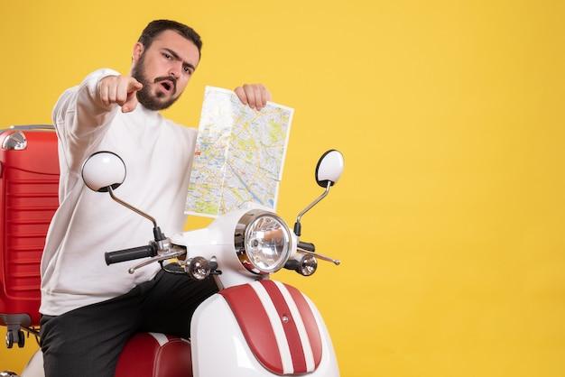Vista superior de um curioso sentado em uma motocicleta com uma mala segurando um mapa apontando para a frente em um fundo amarelo isolado
