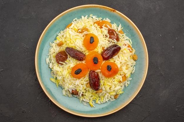 Vista superior de um delicioso arroz plov cozido com diferentes passas dentro do prato na superfície cinza