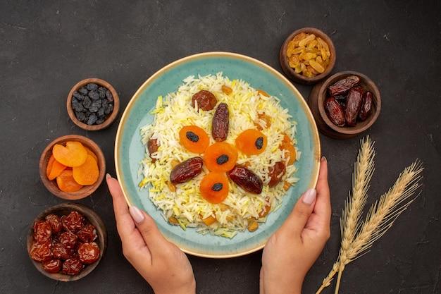 Vista superior de um delicioso arroz plov cozido com diferentes passas dentro do prato na superfície escura