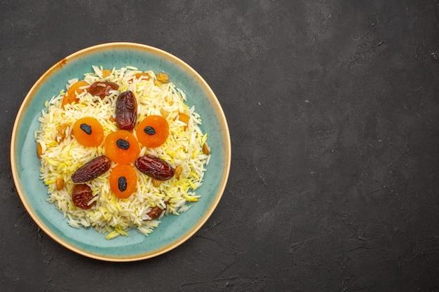 Vista superior de um delicioso arroz plov cozido com passas diferentes dentro do prato em uma superfície cinza escura