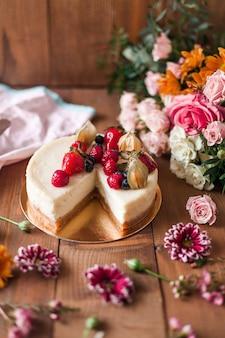 Vista superior de um delicioso bolo com cobertura no topo perto de decorações coloridas de flores em uma mesa de madeira
