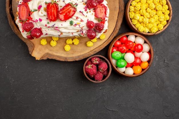 Vista superior de um delicioso bolo cremoso com frutas e doces em preto