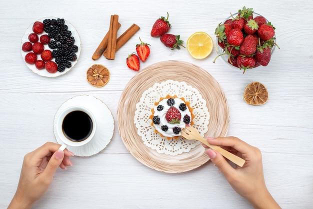Vista superior de um delicioso bolo cremoso com frutas, sendo comido por uma mulher com café com canela em uma mesa branca clara, doce de bolo