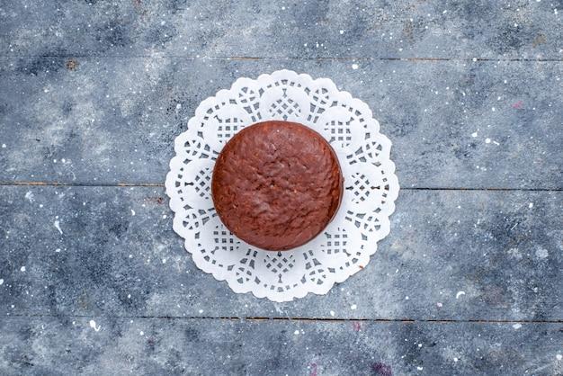 Vista superior de um delicioso bolo de chocolate redondo formado isolado em cinza, assar bolo de chocolate biscoito doce de cacau