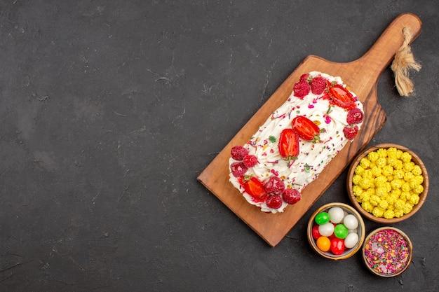 Vista superior de um delicioso bolo de frutas com doces em preto