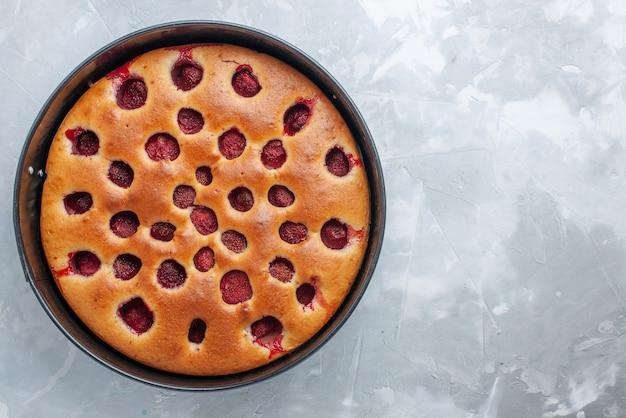 Vista superior de um delicioso bolo de morango assado com morangos vermelhos frescos dentro de uma bandeja na mesa branca, bolo de biscoito doce de frutas