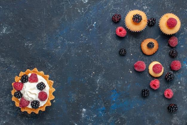 Vista superior de um delicioso bolo doce com diferentes frutas e creme saboroso em um biscoito escuro de bolo de frutas vermelhas