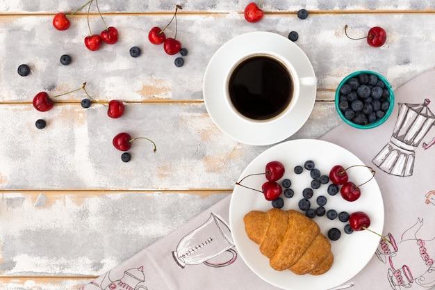 Vista superior de um delicioso café da manhã com croissants, café e mirtilos e cerejas em cima da mesa