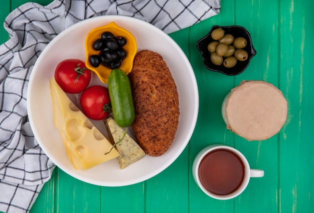 Vista superior de um delicioso hambúrguer de gergelim em um prato branco com queijo de vegetais frescos e azeitonas em um pano xadrez sobre um fundo verde de madeira