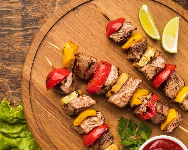 Vista superior de um delicioso kebab na tábua de cortar com limão