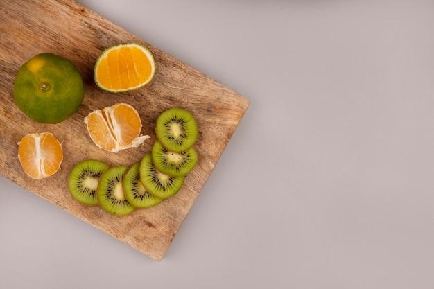 Vista superior de um delicioso kiwi fatiado com tangerinas em uma placa de cozinha de madeira com espaço de cópia