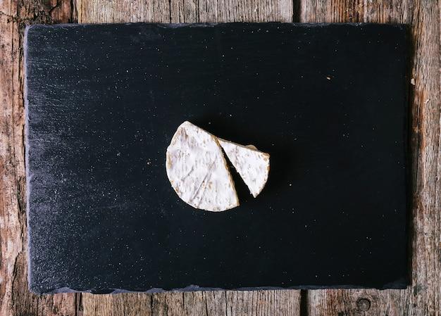 Vista superior de um delicioso queijo no tabuleiro de ardósia