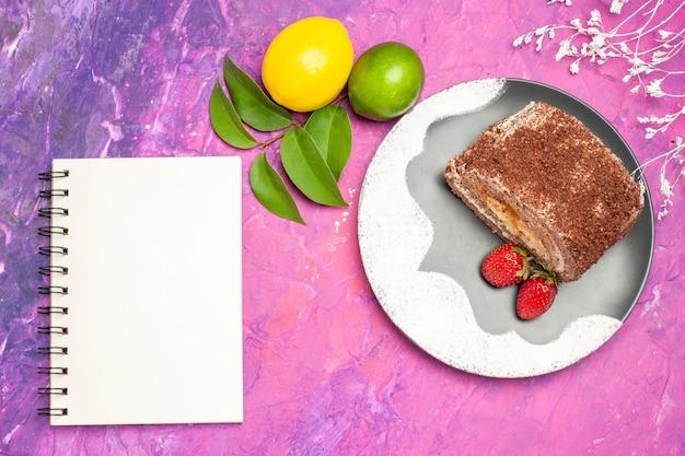 Vista superior de um delicioso rolinho doce com limão na superfície rosa