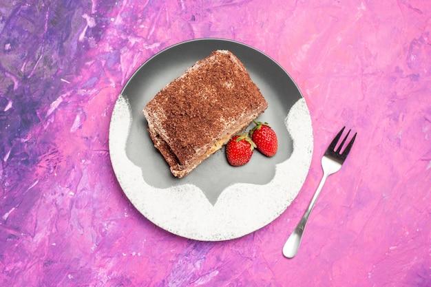 Vista superior de um delicioso rolinho doce com morangos na superfície rosa