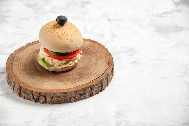 Vista superior de um delicioso sanduíche caseiro com azeitona preta em uma tábua de madeira no lado direito em uma superfície branca manchada
