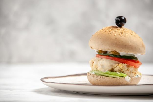 Vista superior de um delicioso sanduíche caseiro em um prato do lado esquerdo em uma superfície branca manchada