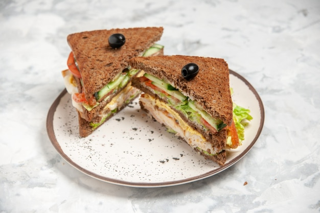Vista superior de um delicioso sanduíche com pão preto decorado com azeitonas em um prato sobre uma superfície branca manchada