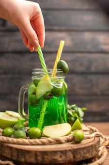 Vista superior de um delicioso suco de fruta fresco servido com a mão de maçã e feijoas segurando um tubo em uma tábua de madeira