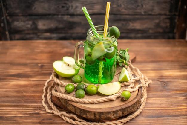 Vista superior de um delicioso suco de fruta fresco servido com maçã e feijoas em uma tábua de madeira