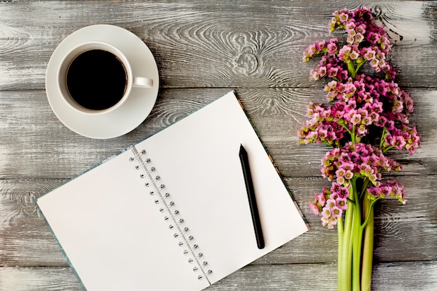 Vista superior de um diário ou caderno, caneta e café e uma flor roxa em uma mesa de madeira cinza. design plano.