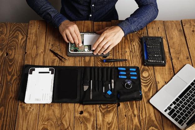 Vista superior de um dispositivo eletrônico limpo profissional na mesa de madeira de seu laboratório perto de suas ferramentas antes de desmontar