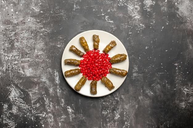 Vista superior de um dolma de folhas saboroso com romãs descascadas em uma mesa escura