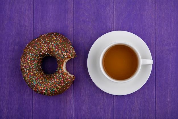 Vista superior de um donut de chocolate mordido com uma xícara de chá em uma superfície roxa brilhante