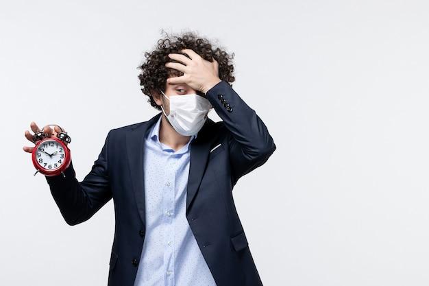 Vista superior de um empresário de terno e máscara segurando um relógio com dor de cabeça