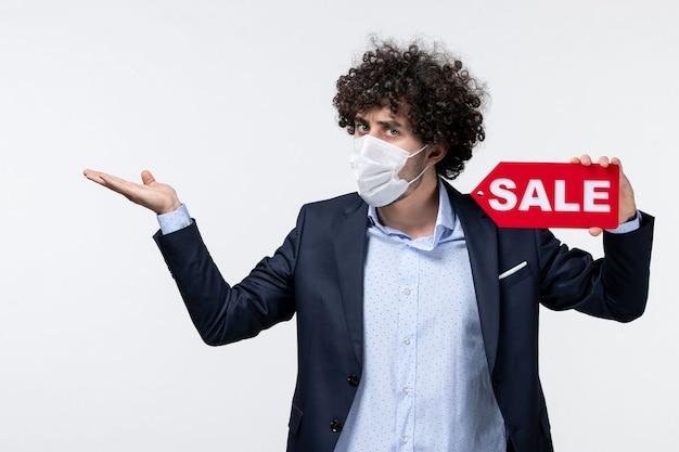 Vista superior de um empresário surpreso e confuso de terno e máscara, mostrando a inscrição de venda