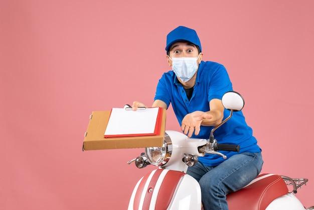 Vista superior de um entregador confuso mascarado, usando um chapéu, sentado na scooter, entregando pedidos segurando um documento em um fundo cor de pêssego