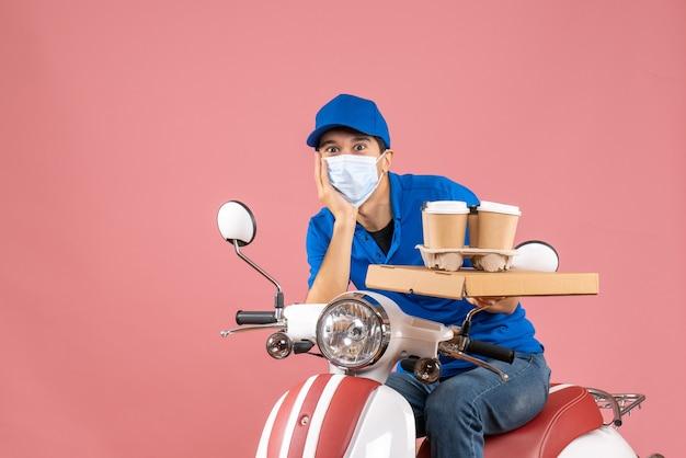 Vista superior de um entregador confuso, mascarado, usando um chapéu, sentado na scooter, entregando pedidos