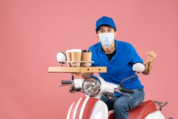 Vista superior de um entregador do sexo masculino louco e emocional com máscara e chapéu, sentado na scooter, entregando pedidos em fundo de pêssego