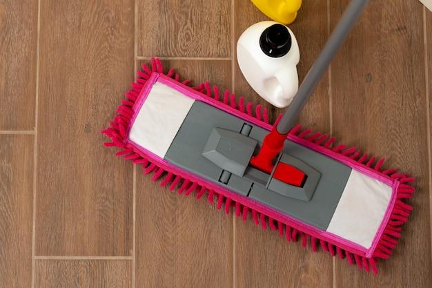 Vista superior de um esfregão rosa no piso de madeira