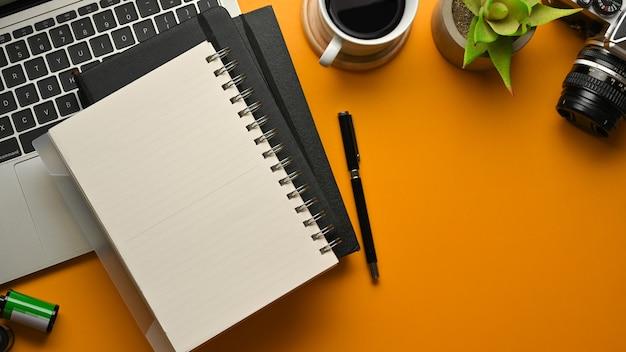 Vista superior de um espaço de trabalho elegante com cadernos, caneta, laptop, câmera, xícara de café e vaso de plantas na mesa amarela