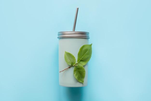 Vista superior de um frasco reusável com uma tampa do metal e uma palha para bebidas do verão.