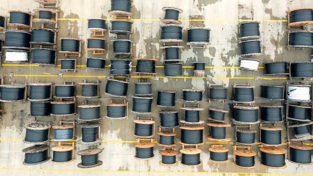 Vista superior de um grande número de carretéis de madeira de um poderoso fio de telecomunicação preto