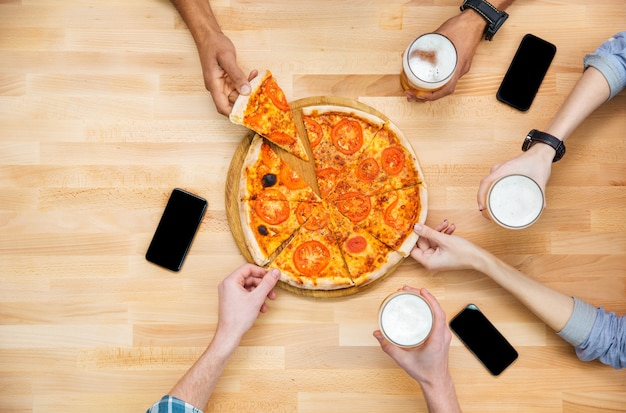 Vista superior de um grupo de alunos se encontrando e comendo pizza juntos