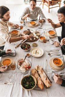 Vista superior de um grupo de amigos internacionais sentados à mesa cheia de comidas diferentes, comendo sonhadoramente