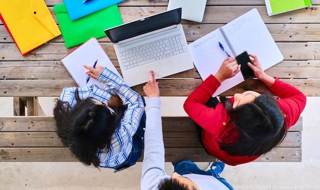 Vista superior de um grupo de estudantes universitários prepara um projeto na frente de um laptop