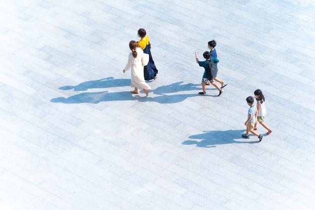 Vista superior de um grupo de mães e crianças caminhando em uma passarela ao ar livre