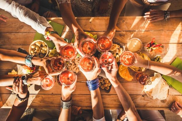 Vista superior de um grupo de mulheres tilintando e se reunindo com vinho tinto e uma mesa cheia de comida - conceito de amizade e celebração