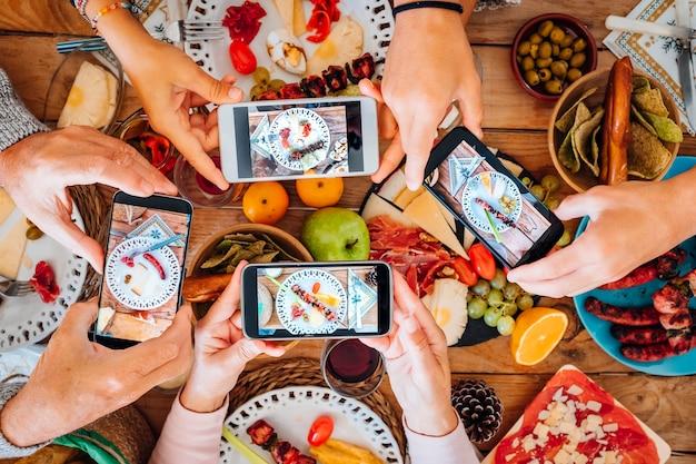 Vista superior de um grupo de pessoas durante a noite de natal tirando fotos de comida e pratos com smartphone todos juntos