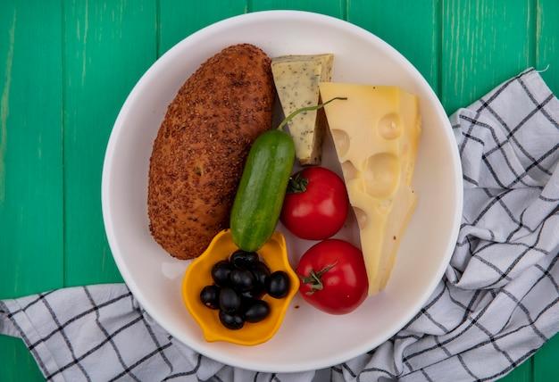 Vista superior de um hambúrguer de gergelim em um prato branco com queijo de vegetais frescos e azeitonas em um pano xadrez em um fundo verde de madeira